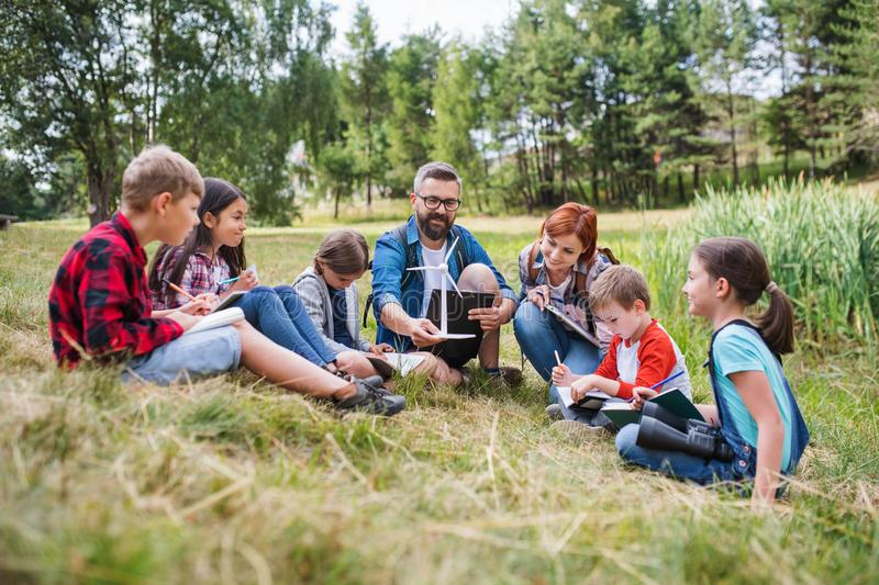 Group of school children with teacher and windmill model on field trip in nature. stock photos