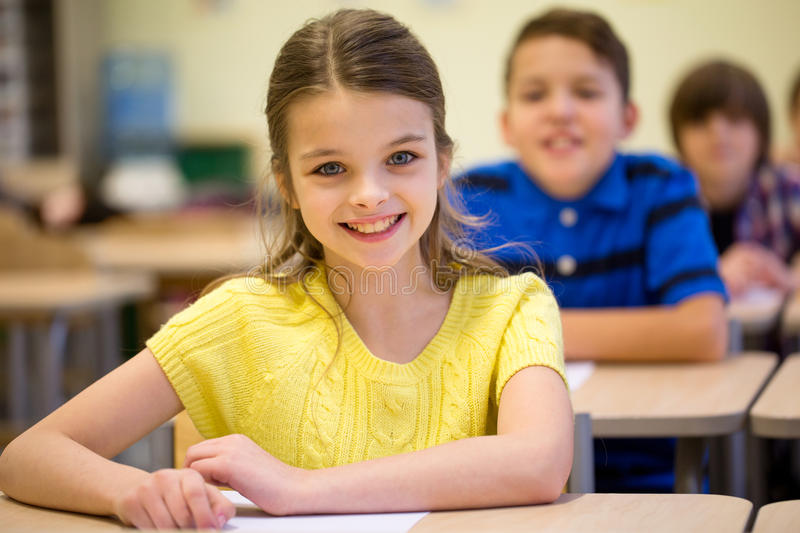 Group of school kids with notebooks in classroom royalty free stock image