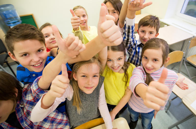 Group of school kids showing thumbs up royalty free stock photography