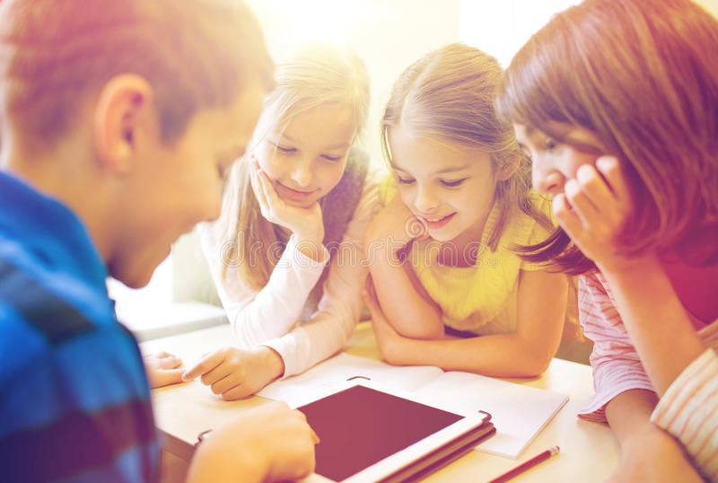 Group of school kids with tablet pc in classroom stock photos