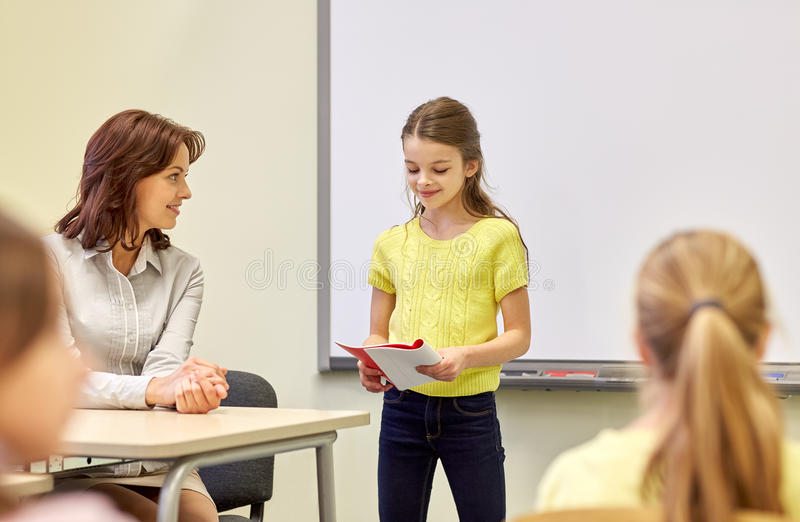 Group of school kids with teacher in classroom. Education, elementary school, learning and people concept - group of school kids with teacher in classroom stock photos