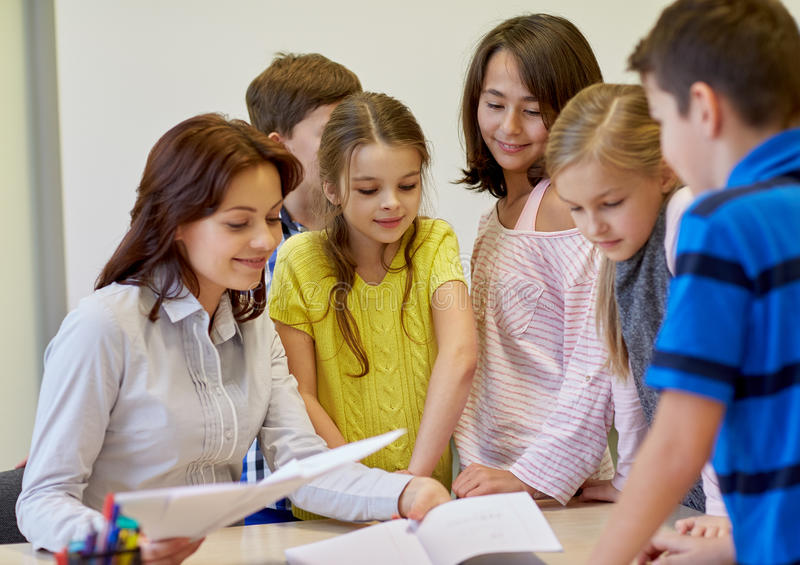 Group of school kids with teacher in classroom. Education, elementary school, learning and people concept - group of school kids with teacher talking in royalty free stock images