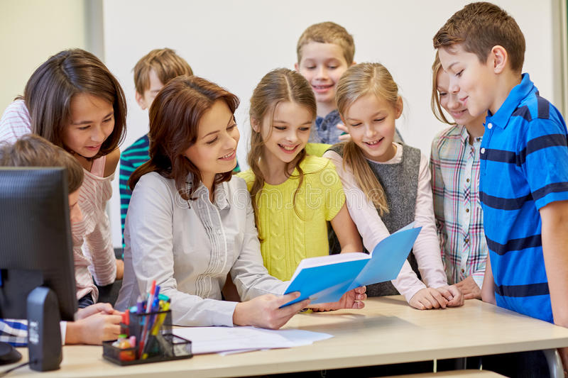 Group of school kids with teacher in classroom. Education, elementary school, learning and people concept - group of school kids with teacher talking in stock photos