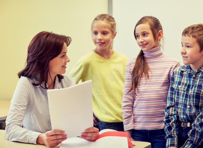 Group of school kids with teacher in classroom stock photo