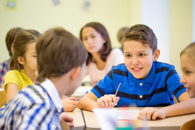 Elementary Classrooms Writing ~ Group of school kids writing test in classroom stock photo