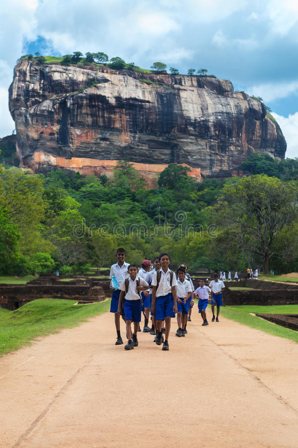 Group of school students walking in garden complex with rock of Sigiriya as backdrop stock image