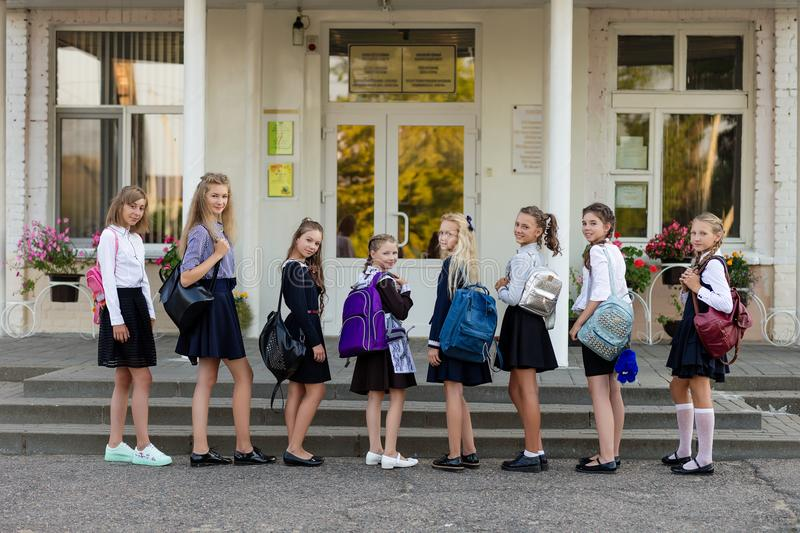A group of schoolgirls with backpacks go to school royalty free stock photography