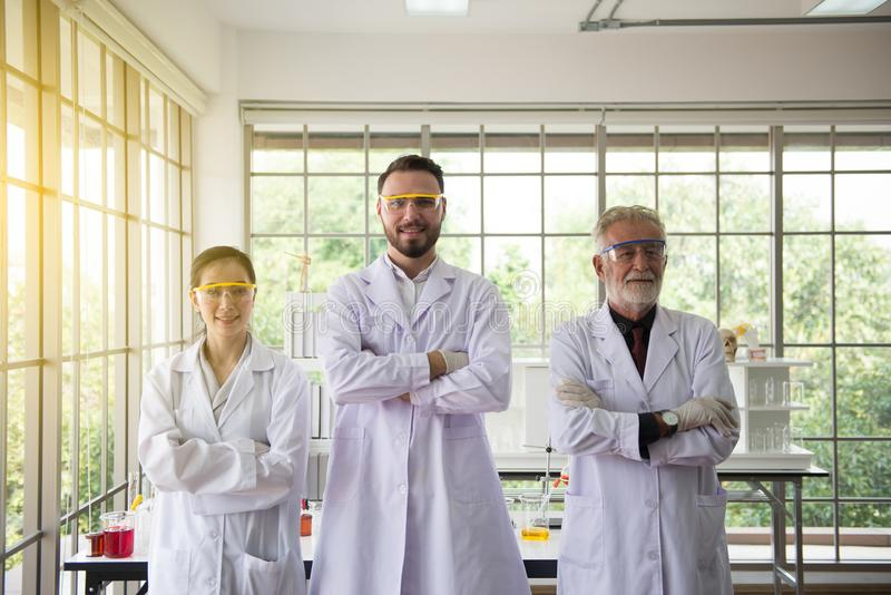 Group of scientist people standing and cross arms together in laboratory,Successful teamwork concept stock photos