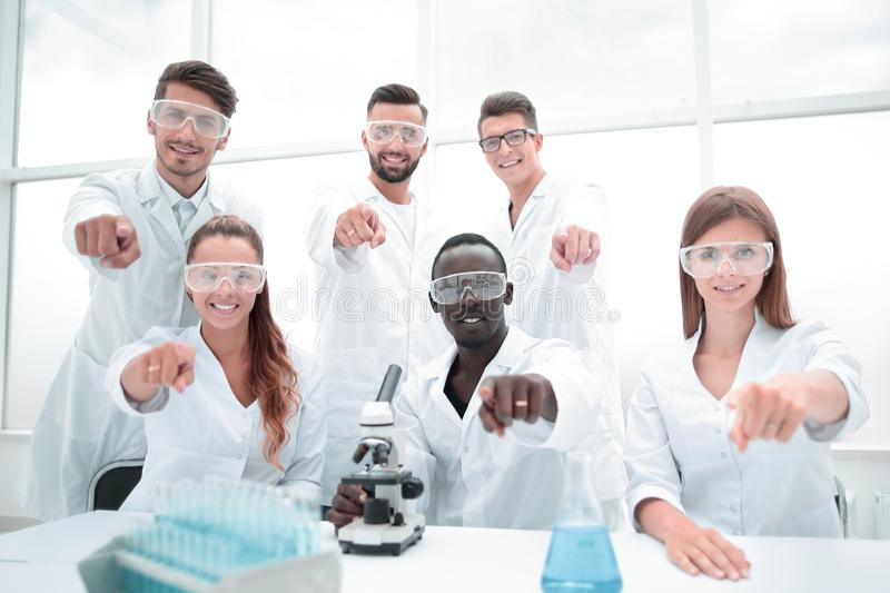 Group of young successful scientists posing for camera stock images