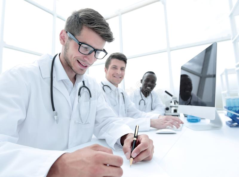 Group of scientists sitting at the laboratory table royalty free stock image