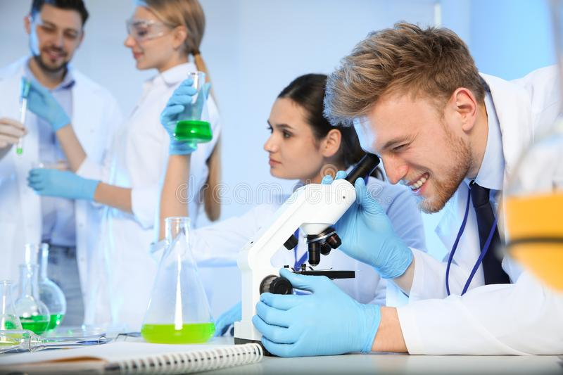 Group of scientists working in chemistry laboratory. Group of scientists working in modern chemistry laboratory stock photo