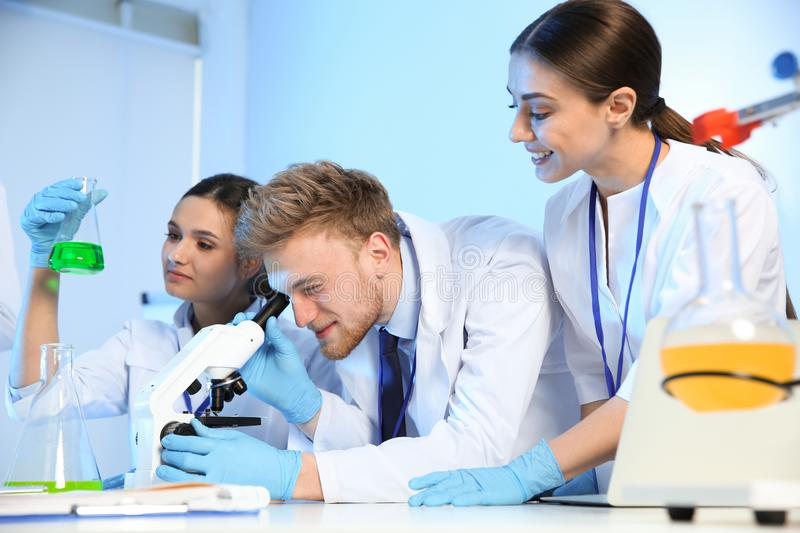 Group of scientists working in chemistry laboratory. Group of scientists working in modern chemistry laboratory stock images