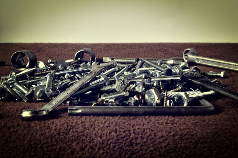 Group of screws and wrenches. Bolts, nuts, screws, wrenches, ring spanners and socket wrenches in a pile on dark background stock images