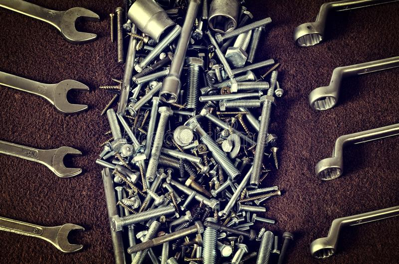 Group of screws and wrenches. Bolts, nuts, screws, wrenches, ring spanners and socket wrenches in a pile on dark background royalty free stock image