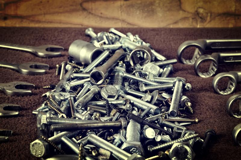 Group of screws and wrenches. Bolts, nuts, screws, wrenches, ring spanners and socket wrenches in a pile on dark background stock image