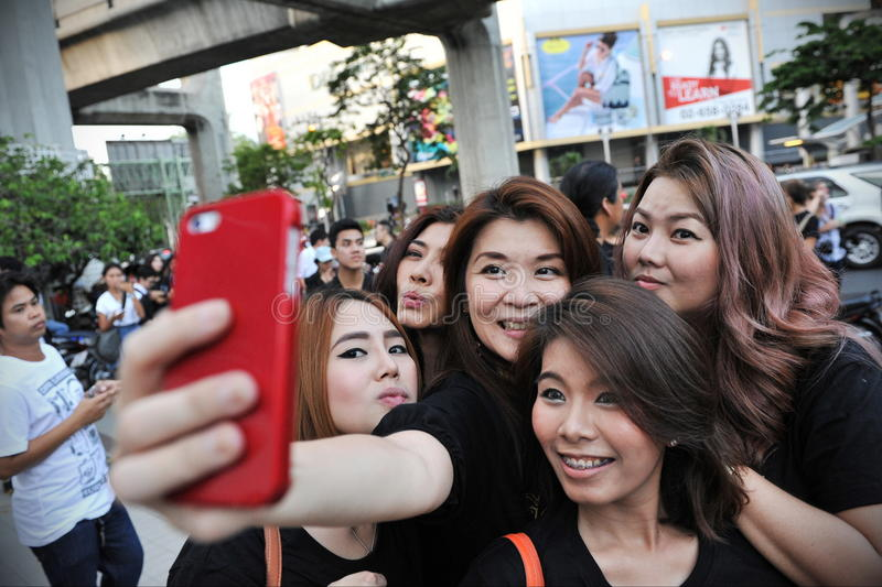 Group Selfie. BANGKOK, THAILAND - MAY 23, 2014: Women pose for a selfie on a city centre street. Research shows the high uptake of social media among Thais with stock photography