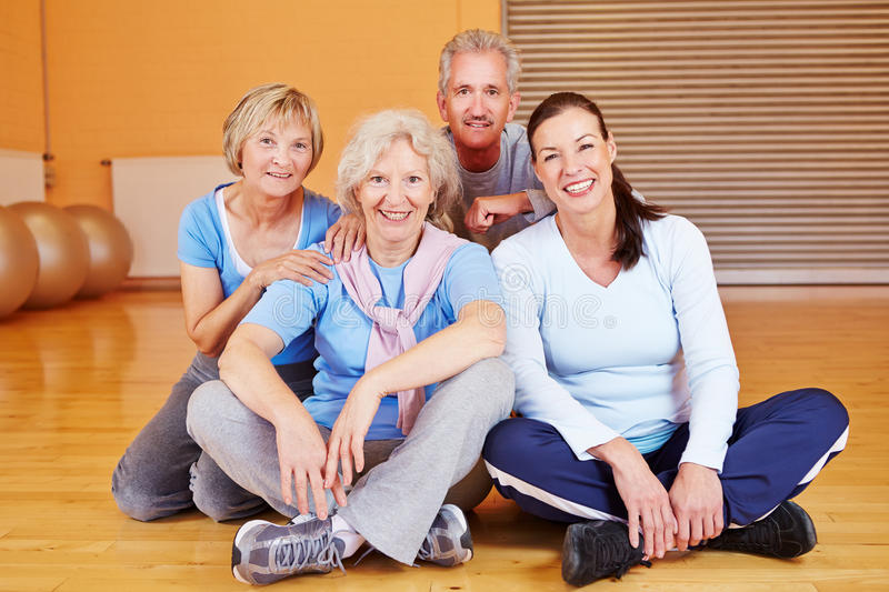 Group of senior citizens in gym. Happy group of senior citizens sitting in a fitness center gym stock photo