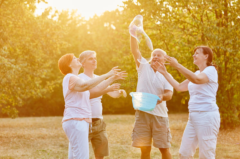 Group of senior citizens making soap bubbles. And having fun in the park stock images