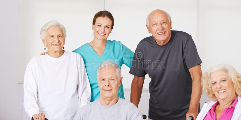 Group of senior citizens in nursing home. Happy group of senior citizens in nursing home with geriatric nurse stock photos