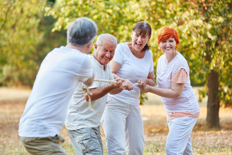 Group of senior citizens playing tug of war. In summer in the park stock image