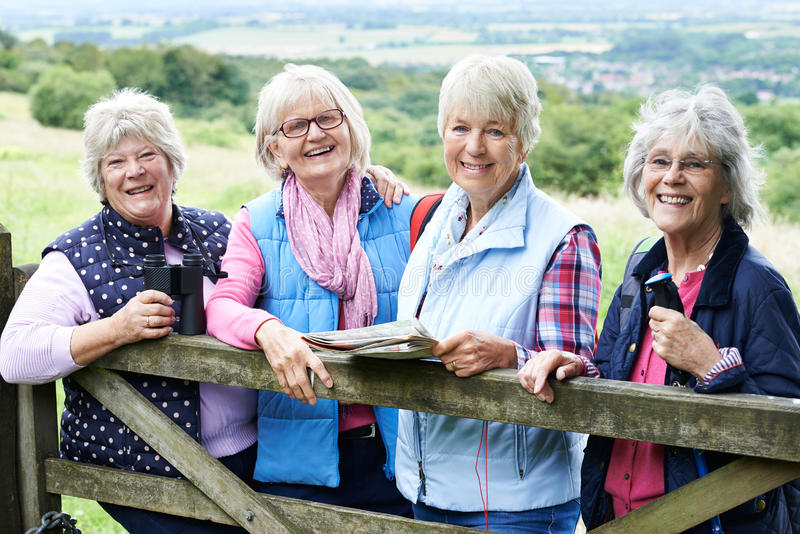 Group Of Senior Female Friends Hiking In Countryside royalty free stock image