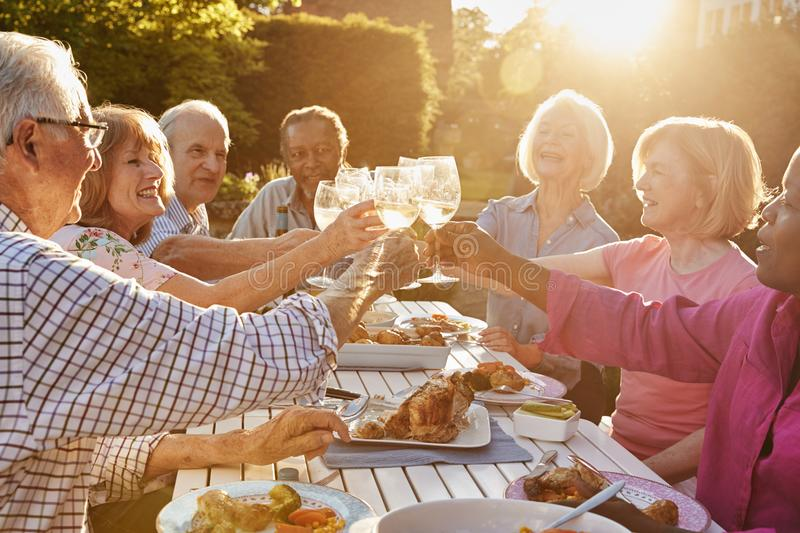 Group Of Senior Friends Making A Toast At Outdoor Dinner Party stock photography