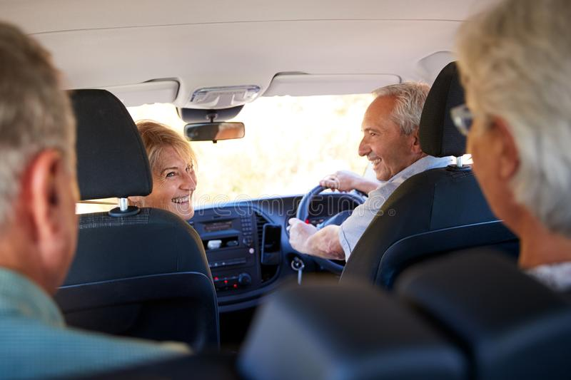 Group Of Senior Friends Sitting In Car Driving To Vacation stock photo