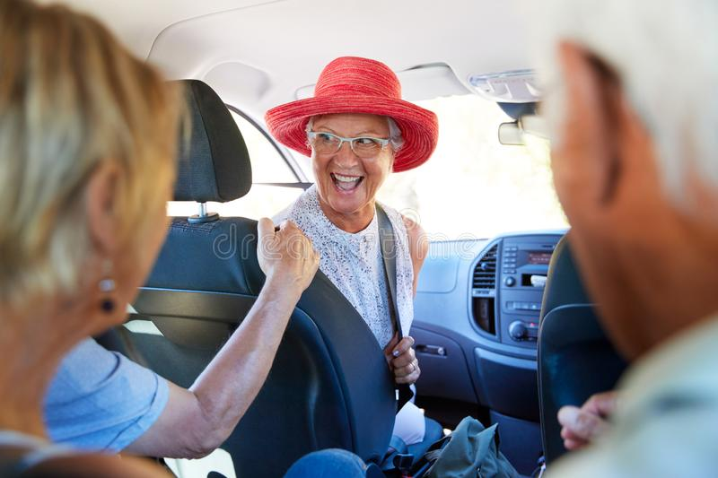 Group Of Senior Friends Sitting In Car Driving To Vacation royalty free stock image
