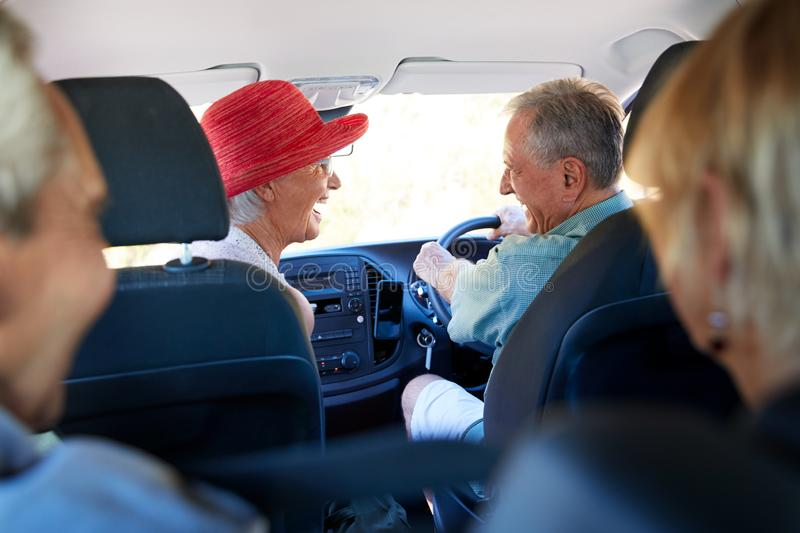 Group Of Senior Friends Sitting In Car Driving To Vacation stock image