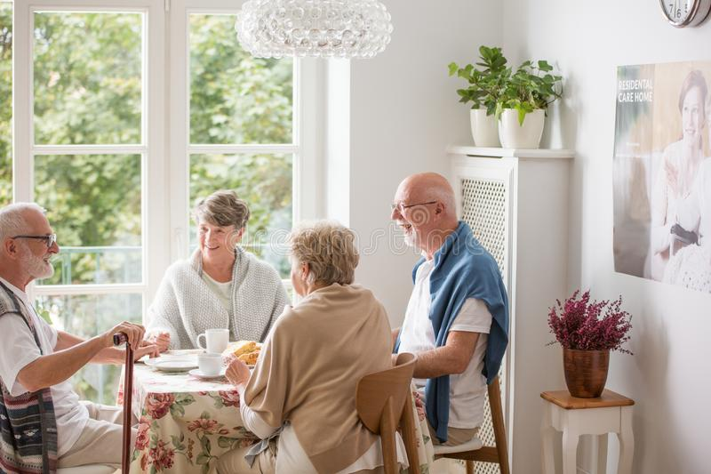 Group of senior sitting together at nursing home dining room royalty free stock photo