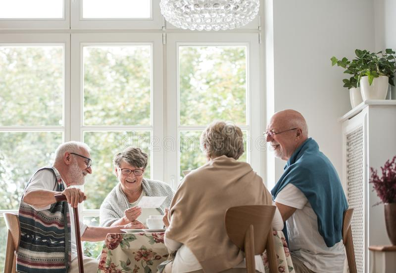 Group of senior sitting together at nursing home dining room stock photo