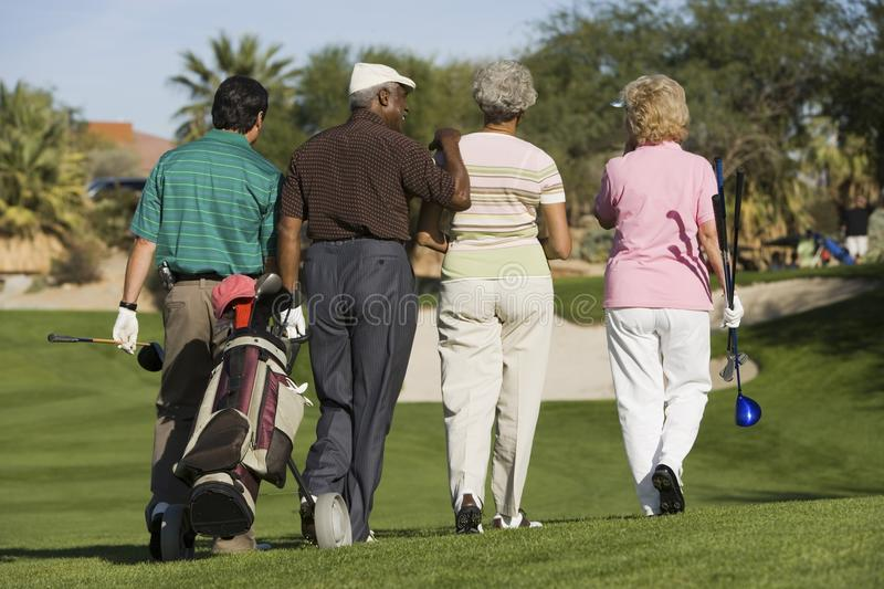 Group of senior golfers walking on golf course stock photo