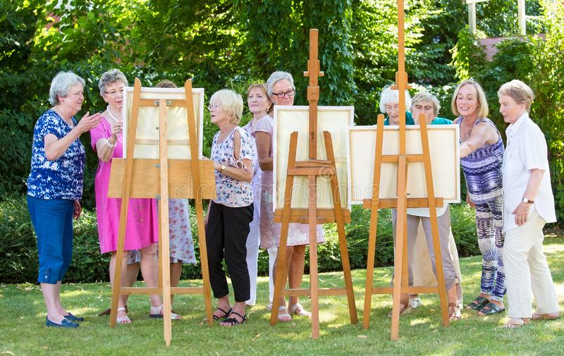 Group of senior ladies enjoying an art class outdoors in a park or garden as a therapeutic recreational activity at a care home. stock images