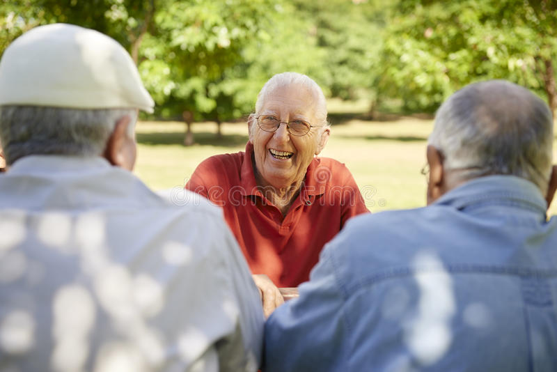 Group of senior men having fun and laughing in park. Active retired senior people, old friends and leisure, group of three elderly men having fun, laughing and stock image