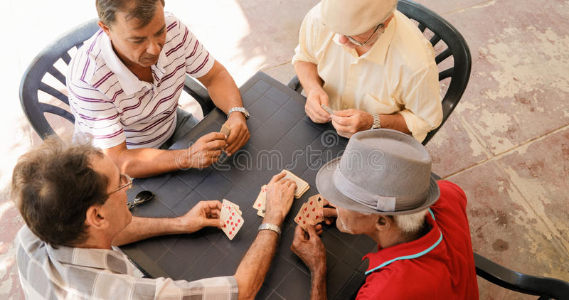 Group Of Senior Men Playing Cards Game In Patio royalty free stock photos