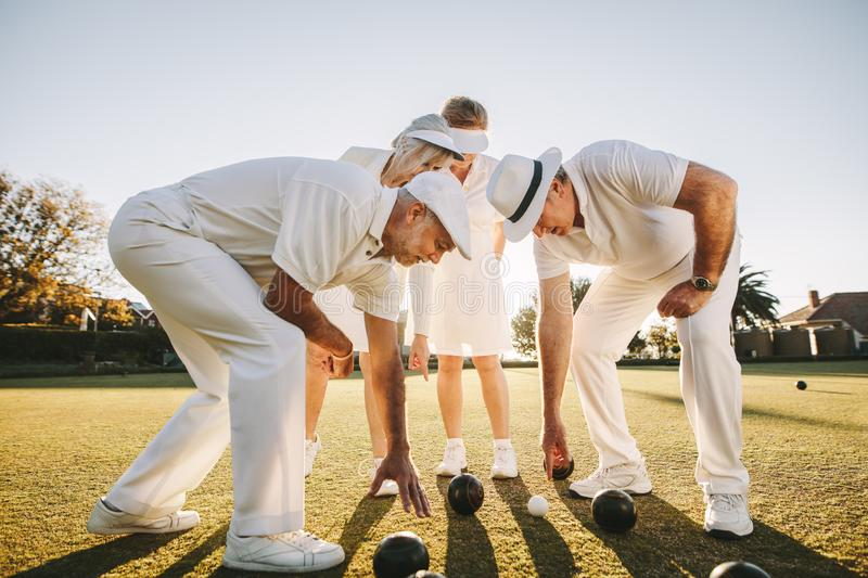 Group of senior men and women playing boules in a lawn royalty free stock images