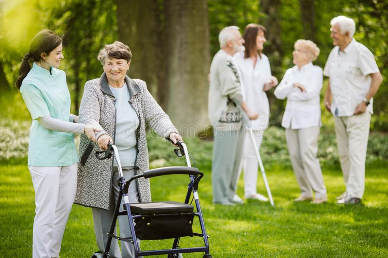 Senior patients with caregiver in the garden of nursing home stock images
