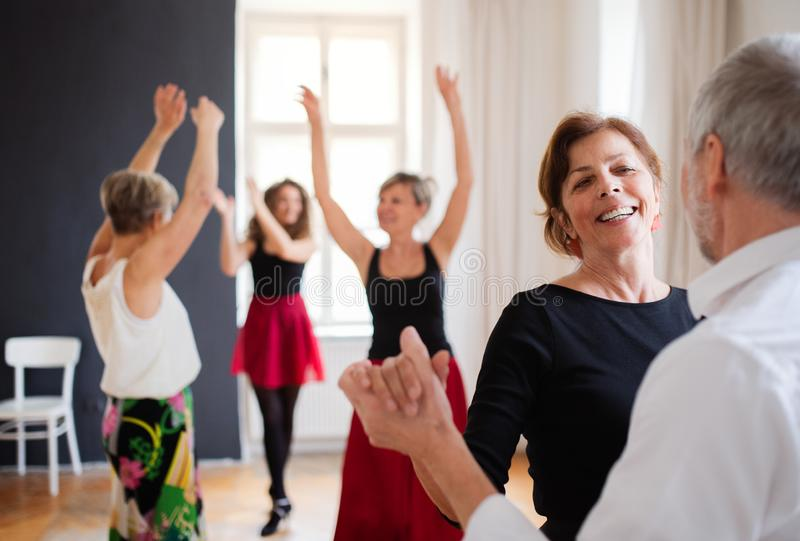 Group of senior people in dancing class with dance teacher. stock photos