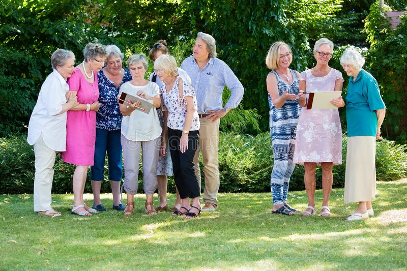 Group of senior people discussing their paintings together with course instructor, while standing in garden on sunny day stock photography