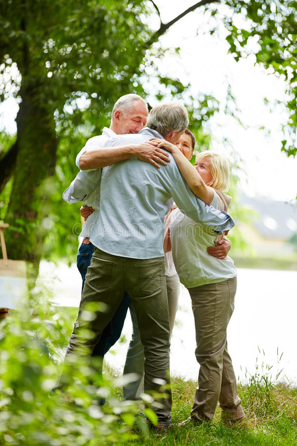 Group of senior people embracing in nature stock photography