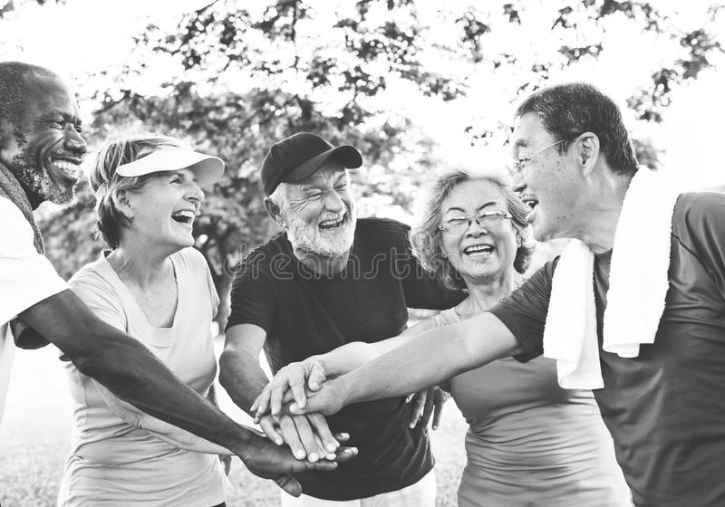 Group Of Senior Retirement Exercising Togetherness Concept. Diverse seniors people exercising outdoor hands together royalty free stock image
