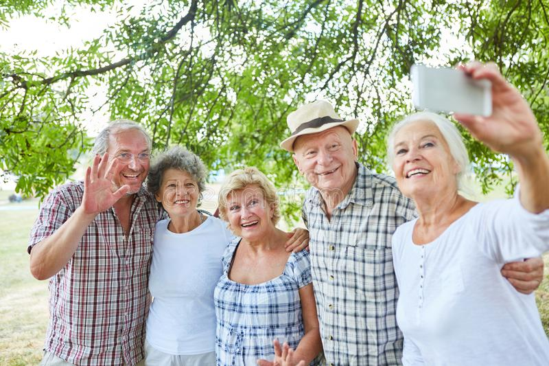 Group of seniors as friends take a selfie. With the smartphone in nature stock image