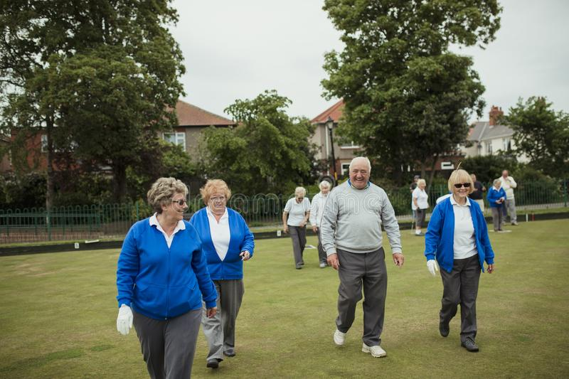 Group of Seniors at Bowling Green. A front view shot of a group of seniors walking in a bowling green stock photos