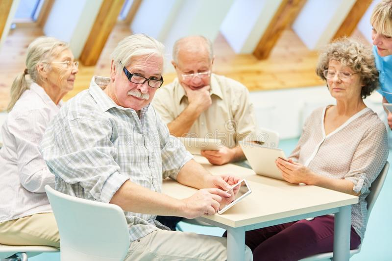 Group of seniors in computer course at retirement home. Group seniors in the computer course in the nursing home cared for by a caregiver royalty free stock image