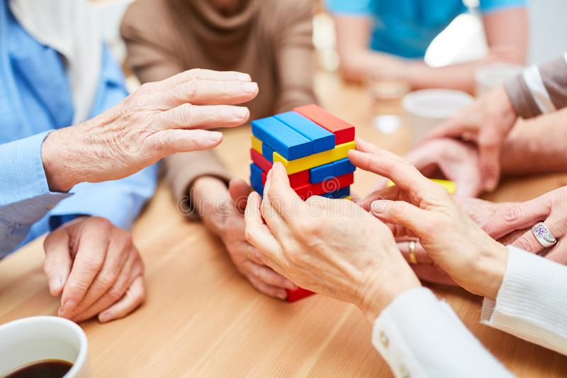 Group of seniors builds tower of building blocks stock photography