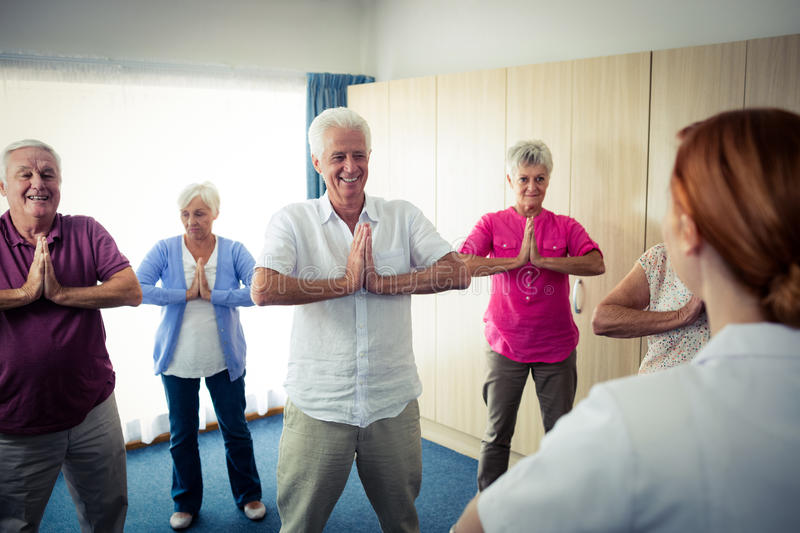 Group of seniors doing exercises with nurse royalty free stock image