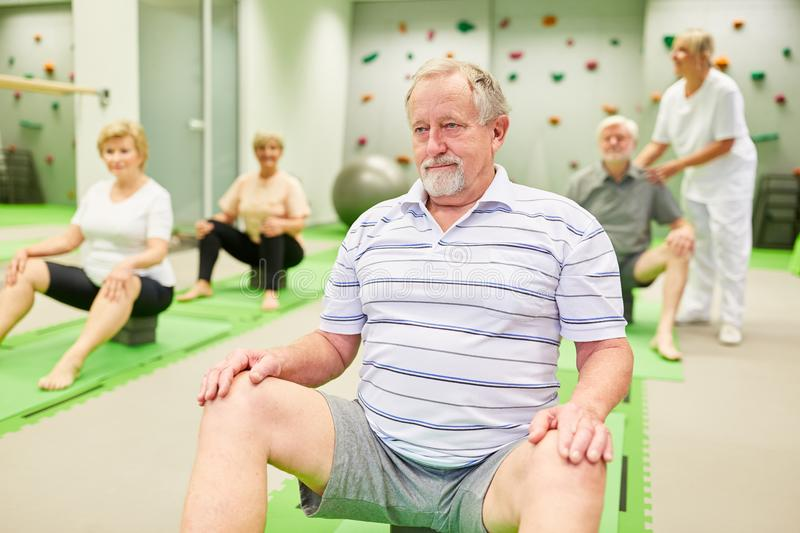 Group of seniors doing physiotherapy with guidance. In a physiotherapy course stock images