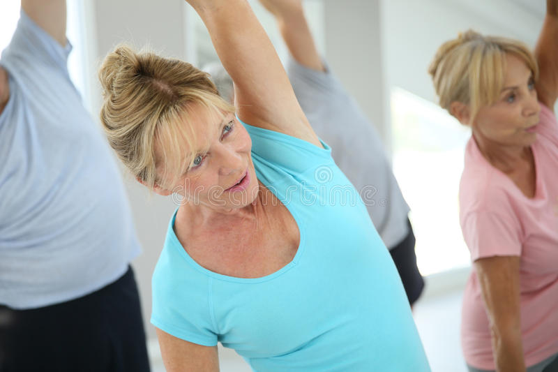 Group of seniors doing stretching. Senior people stretching out in fitness room stock image