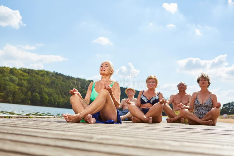 Group of seniors doing yoga exercise on the lake. In summer for relaxation and health royalty free stock image