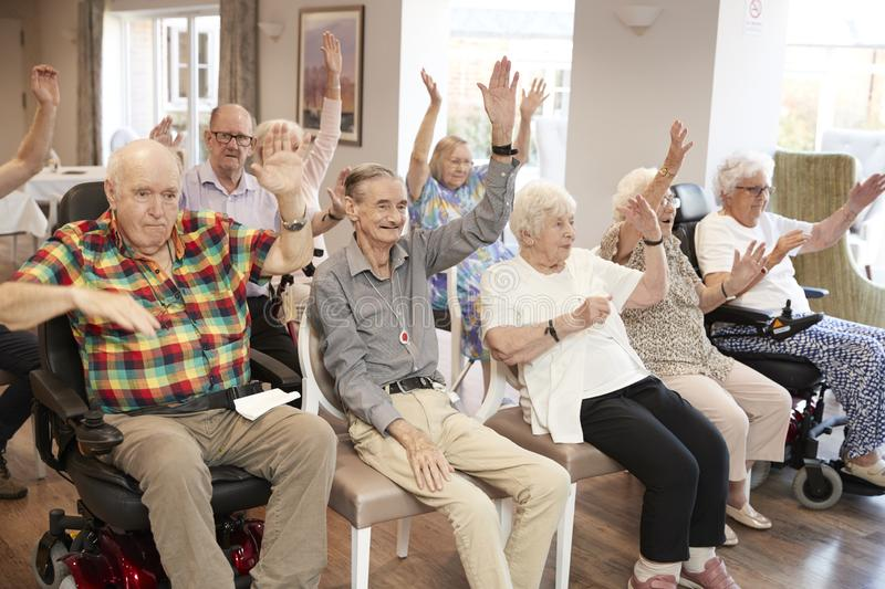 Group Of Seniors Enjoying Fitness Class In Retirement Home stock image